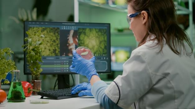 Mujer química que analiza la carne de vacuno vegana para el experimento de bioquímica