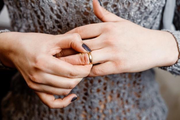 Mujer se quita un anillo de compromiso, conflicto familiar, primer plano