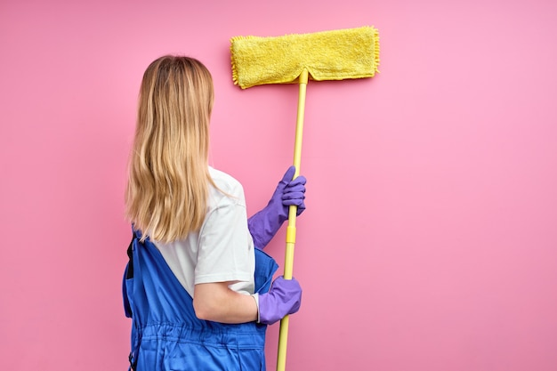 Mujer quita las telarañas de las paredes con un trapeador, vista trasera de una señorita en uniforme de trabajo azul y guantes de goma