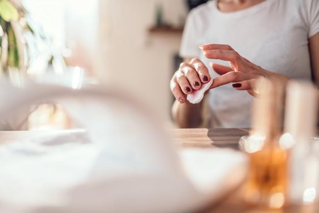 Mujer quitando esmalte de uñas