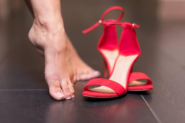 Mujer quitándose las sandalias rojas de tacón alto