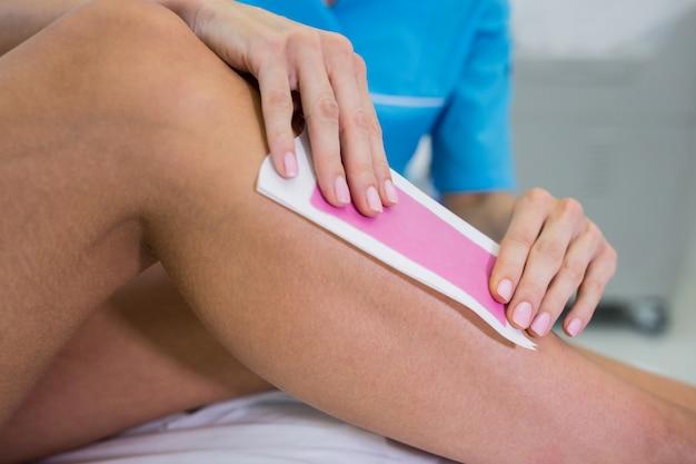 Mujer quitándose el vello de la pierna