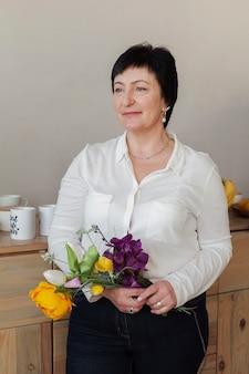 Mujer con ramo de flores y mirando a otro lado