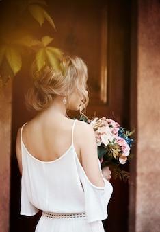 Una mujer con un ramo de flores en sus manos está esperando a su amado hombre cerca de la casa. peinado perfecto, cabello rizado. historia de amor
