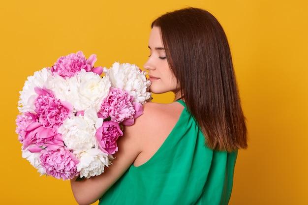 Mujer con ramo de peonías rosas y blancas en las manos, posando hacia atrás, niña en vestido transparente claro
