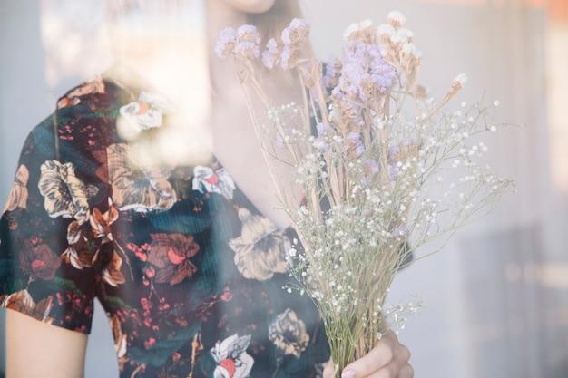 Mujer con ramo de plantas secas detrás de la ventana