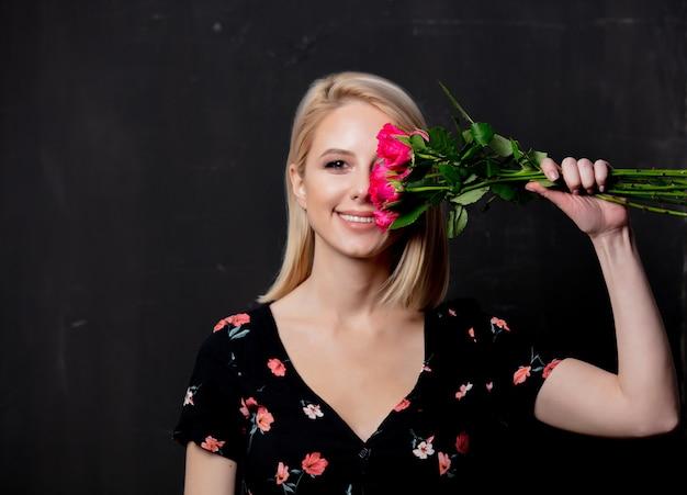 Mujer con un ramo de rosas sobre un fondo oscuro