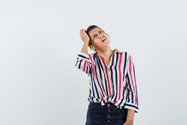 Mujer rascándose la cabeza en camisa, falda y mirando olvidadiza.