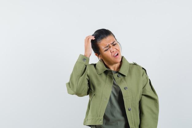 Mujer rascándose la cabeza con chaqueta, camiseta y mirando vacilante.