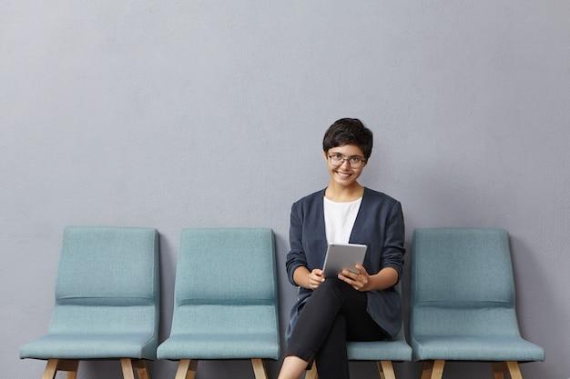 Mujer de raza mixta de aspecto agradable tiene un peinado corto de moda, usa gafas y chaqueta formal, viene a la entrevista de trabajo,