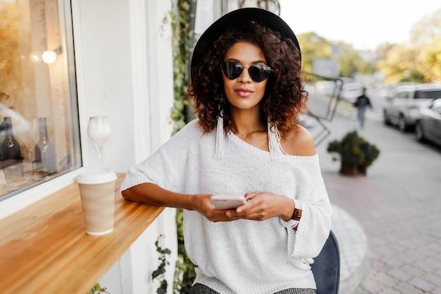 Mujer de raza mixta itinerante en elegante traje casual relajante al aire libre en el café de la ciudad, tomando café y hablando por teléfono móvil. usando accesorios de moda y gafas de sol.
