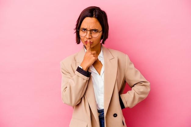 Mujer de raza mixta de negocios joven aislada en la pared rosa pensando y mirando hacia arriba, siendo reflexivo, contemplando, teniendo una fantasía.