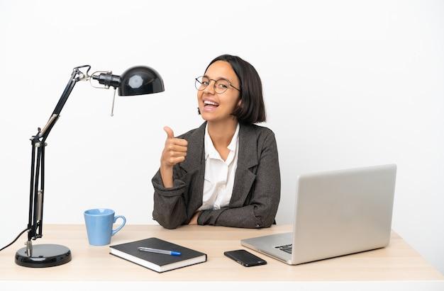 Mujer de raza mixta de negocios joven que trabaja en la oficina con los pulgares hacia arriba porque ha sucedido algo bueno