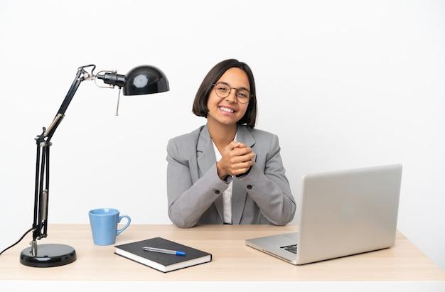 Mujer de raza mixta de negocios joven que trabaja en la oficina sonriendo y mostrando el signo de la victoria