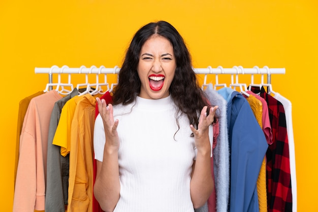 Mujer de raza mixta en una tienda de ropa infeliz y frustrada con algo