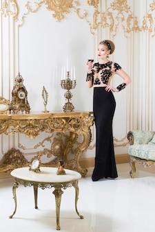 Mujer real rubia de pie junto a la mesa retro en un magnífico vestido de lujo con una copa de vino en la mano. interior. espacio de copia