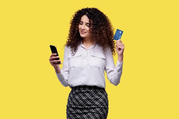 La mujer realiza compras en una tienda en línea mediante teléfono y tiene tarjeta de crédito bancaria