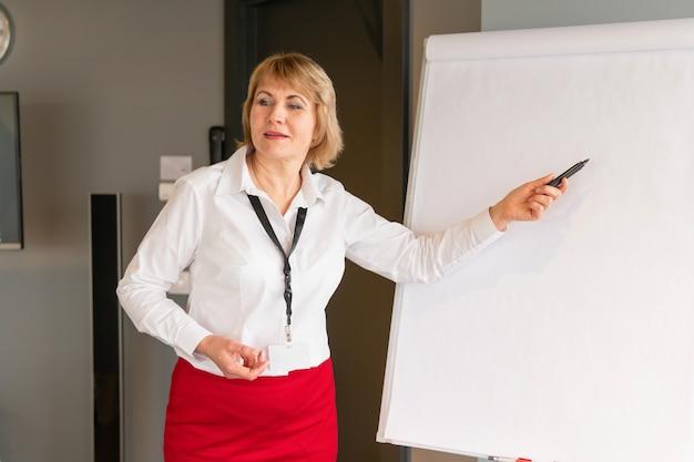 Una mujer realiza una formación en un centro de negocios. coaching de mujer de mediana edad en el tablero de rotafolio en estilo empresarial.