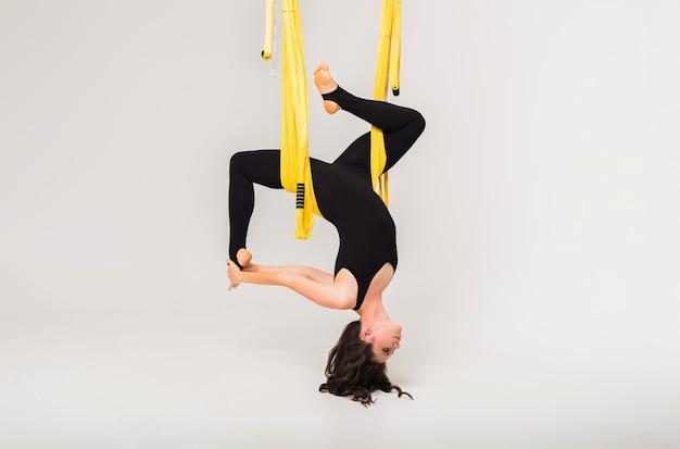 Mujer realiza una pose de yoga antigravedad invertida en una hamaca amarilla sobre un fondo blanco aislado con una copia del espacio. vista lateral