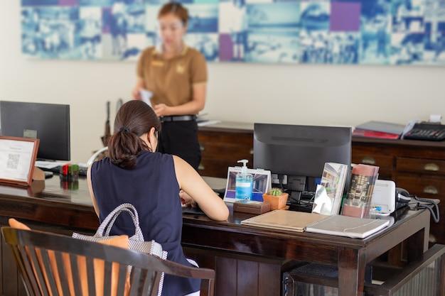 Mujer recepcionista en el hotel con careta con mujer check in en el hotel.