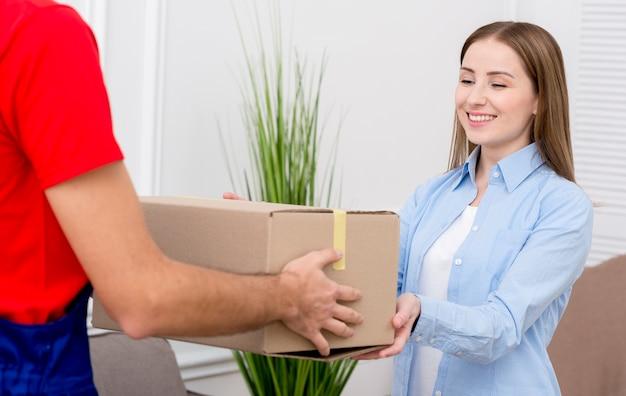 Mujer recibe una caja de cartón de mensajería