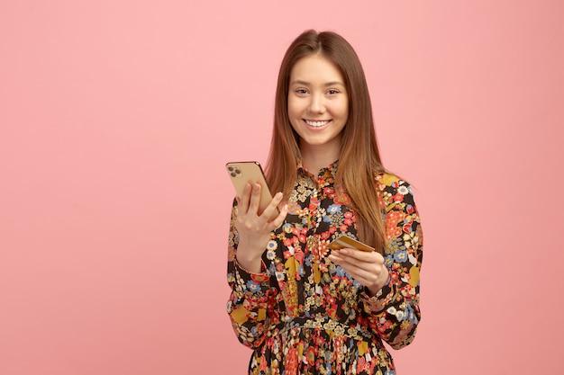 La mujer recibe el servicio bancario, una compra en línea, usando una tarjeta de crédito con una oferta de estudiante, tiene un teléfono móvil en las manos.