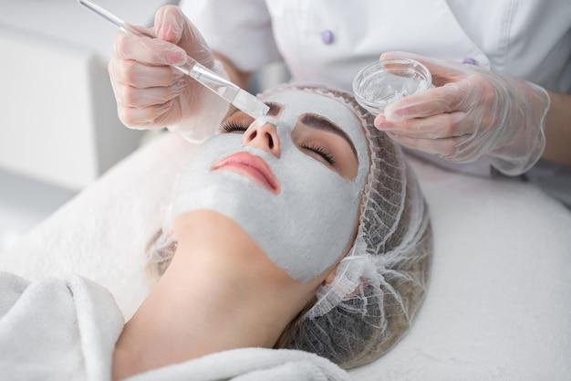 Mujer recibiendo cuidado facial por esteticista en el salón de spa