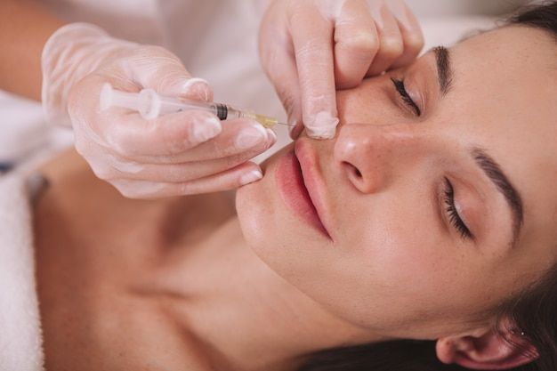 Mujer recibiendo inyecciones de relleno en la clínica de belleza