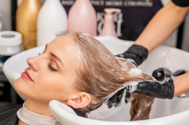 Mujer recibiendo lavarse el cabello en una peluquería
