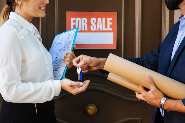 Mujer recibiendo llave de agente inmobiliario