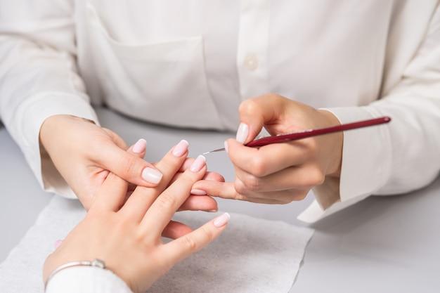 Mujer recibiendo manicura francesa por esteticista