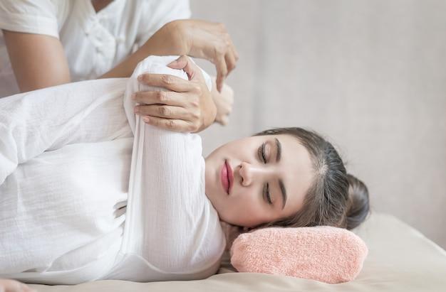 La mujer está recibiendo un masaje en el brazo por un terapeuta de masaje tailandés