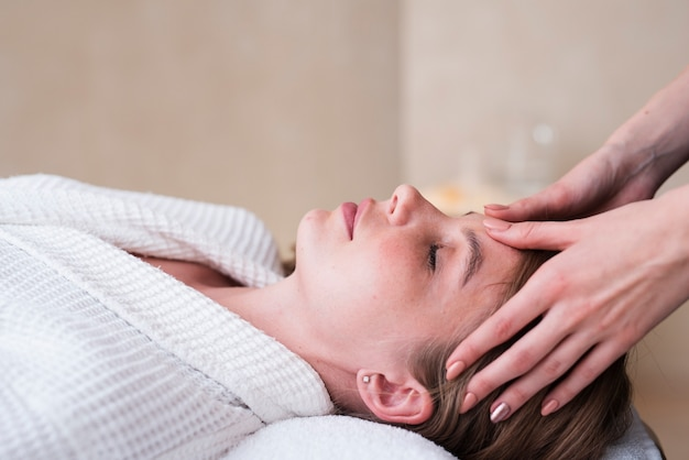 Mujer recibiendo masaje de cabeza en el spa