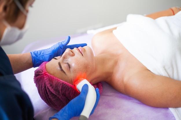 Mujer recibiendo masaje de hardware de glp en la clínica.
