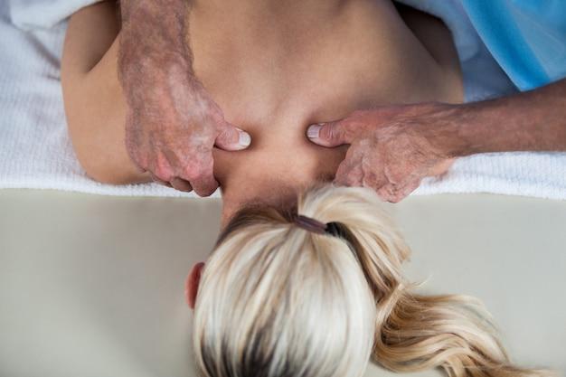 Mujer recibiendo masaje de hombro de fisioterapeuta