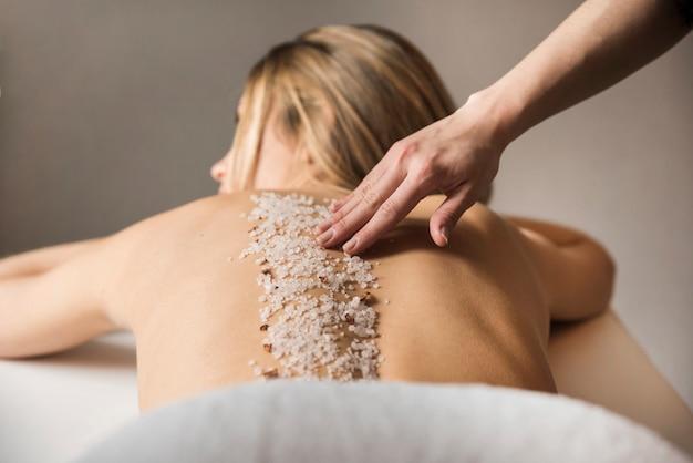Mujer recibiendo masaje con sal de mar en spa