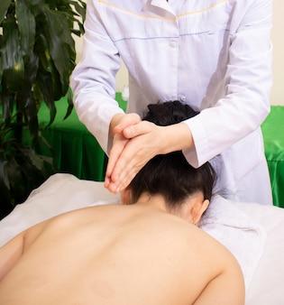 Mujer recibiendo masaje tailandés de compresas herbales en spa