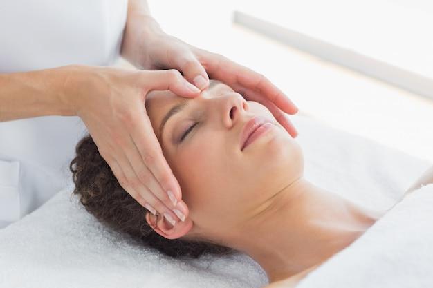 Mujer recibiendo masajes en la frente