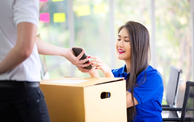 Mujer recibiendo el paquete del repartidor y firmar en tableta