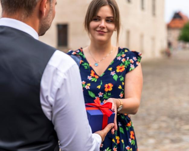 Mujer recibiendo un regalo de su amigo