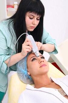 Mujer recibiendo terapia de limpieza con un equipo de ultrasonidos profesional en la oficina de cosmetología