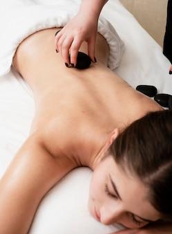 Mujer recibiendo terapia de roca calentada en el spa