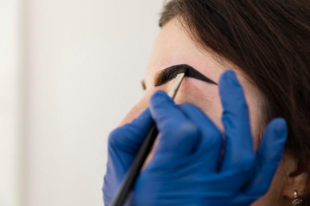 Mujer recibiendo un tratamiento de cejas en un salón de belleza