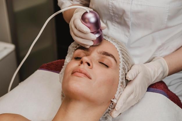 Mujer recibiendo un tratamiento cosmético en el centro de bienestar