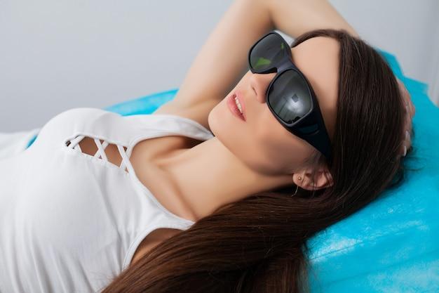Mujer recibiendo tratamiento con láser en un salón de belleza