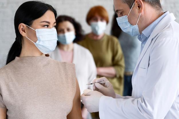 Mujer recibiendo vacuna inyectada por médico con máscara médica