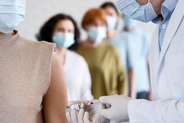 Mujer recibiendo vacuna inyectada por médico masculino