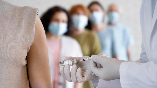 Mujer recibiendo vacuna inyectada por médico