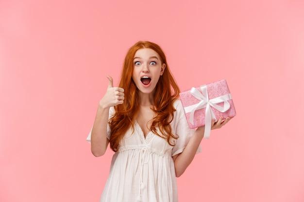 La mujer recibió lo que quería en el cumpleaños. impresionada y feliz, alegre pelirroja linda hembra