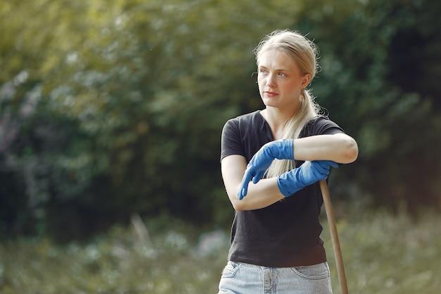 Mujer recoge hojas y limpia el parque.